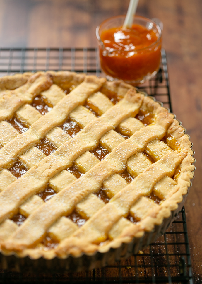 crostata out of the oven resting on a cooling rack, peach jam on the side.