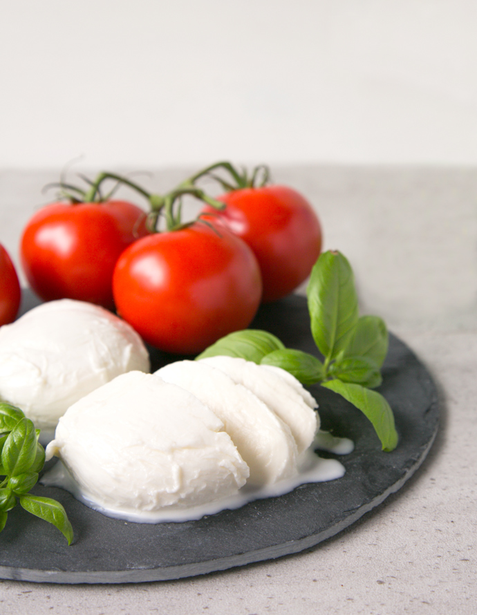 homemade mozzarella balls served with tomatoes and basil leaves.