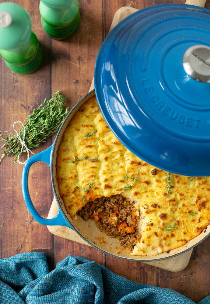 cottage pie in a cast iron casserole pot, topped with fresh thyme sprigs.