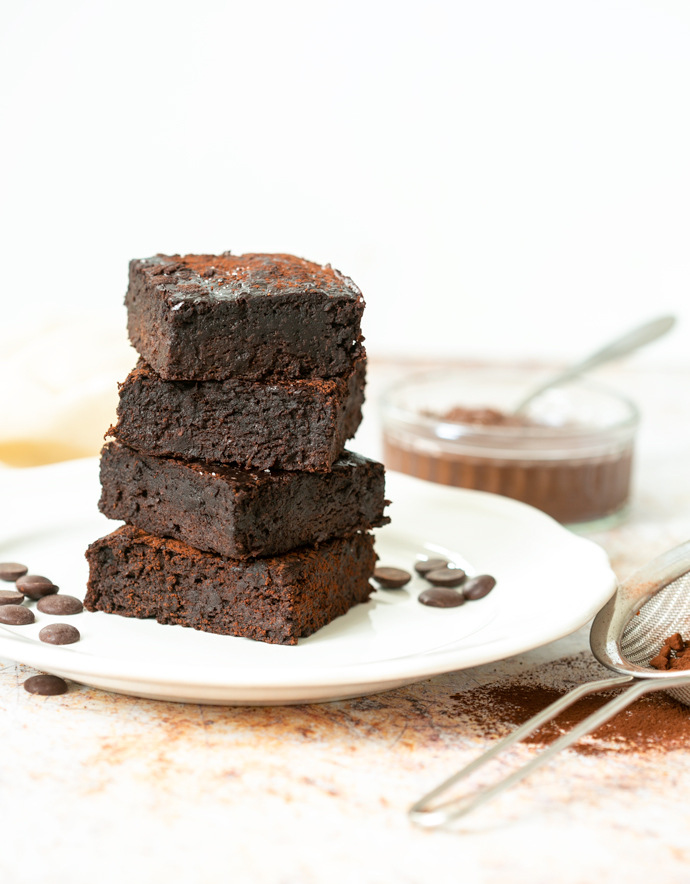 4 3-ingredient brownies on top of each other on a plate.