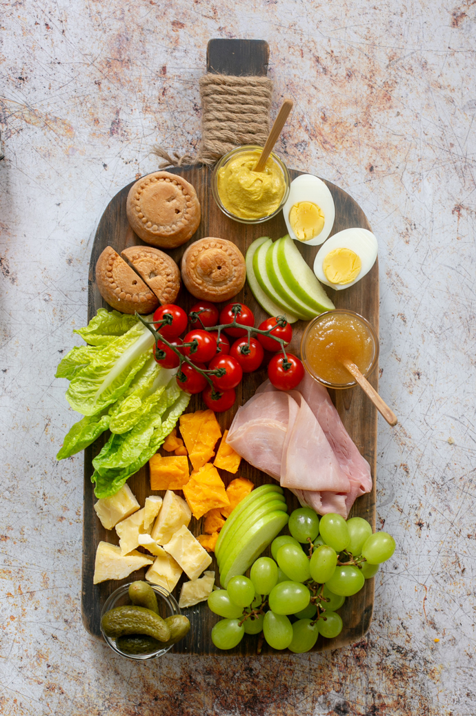 The Ploughman's lunch board featuring: pork pies, mustard, boiled eggs, cherry tomatoes, gem lettuce, cheddar, ham slices, grapes, gherkins, chutney.