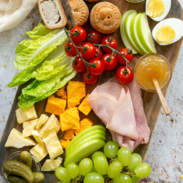Ploughman's lunch board image showcasing pork pies, mustard, boiled eggs, sliced apple, gem lettuce leaves, ham slices, cheddar cheese, grapes and gherkins.