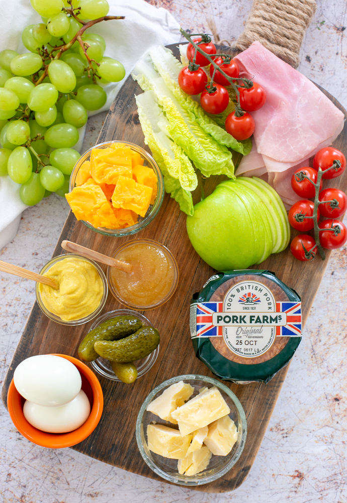 Recipe ingredients: grapes, ham slices, cherry tomatoes, cheddar cheese, pork pie, sliced green apple, boiled eggs, gherkins, mustard, chutney, gem lettuce.