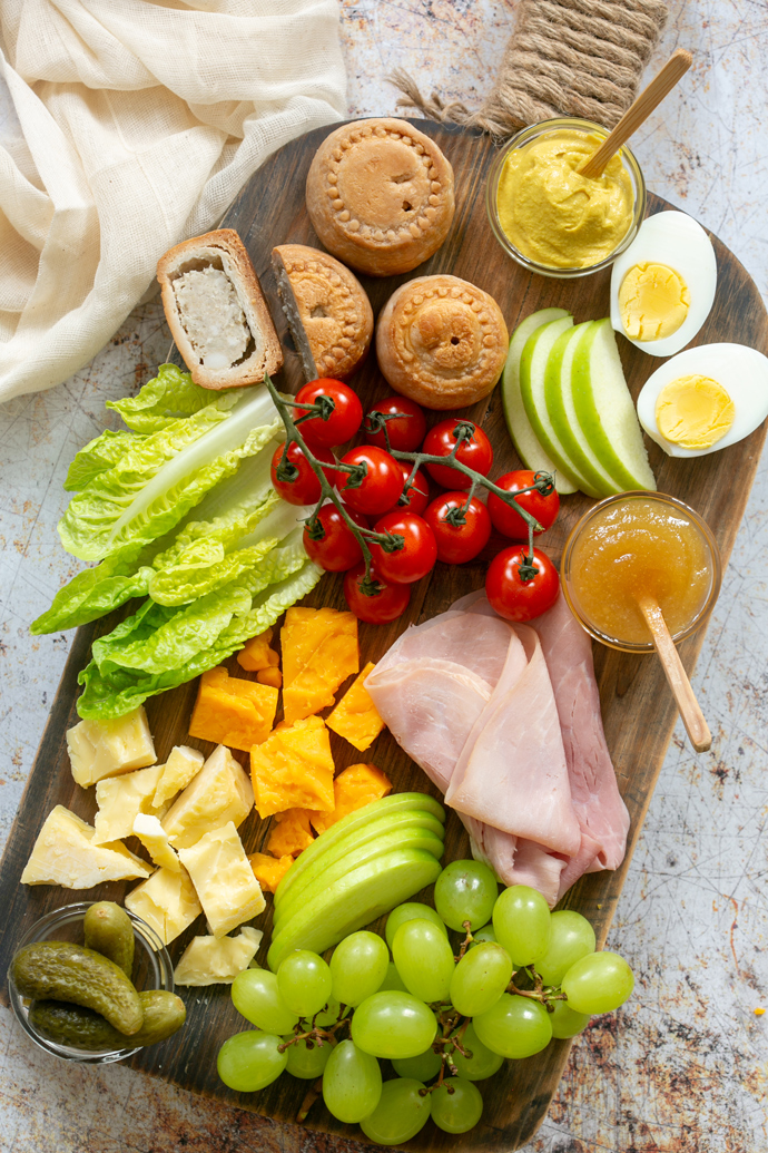 Ploughman's lunch board showcasing pork pies, mustard, boiled eggs, sliced apple, gem lettuce leaves, ham slices, cheddar cheese, grapes, gherkins.