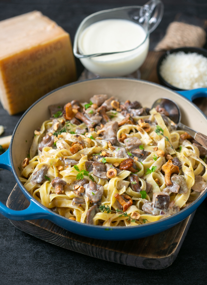 tagliatelle pasta with parmesan sauce, wild mushrooms and roasted hazelnuts, in a large cast iron shallow pot. Served next Parmigiano Reggiano cheese wedge and extra sauce on the side.