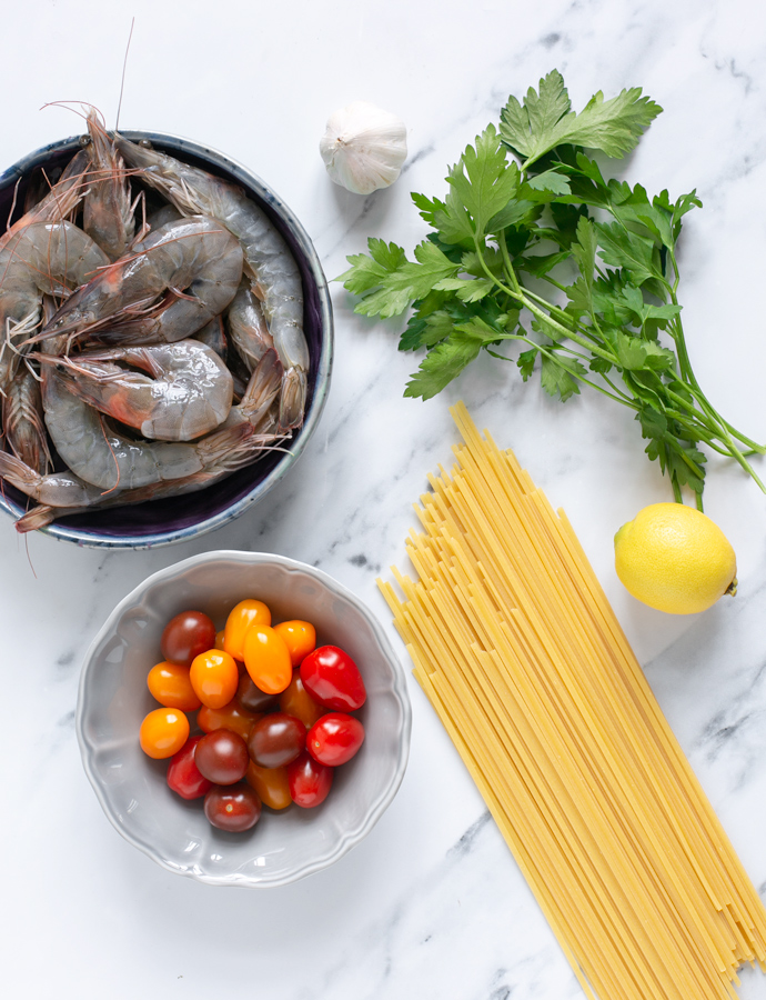 recipe ingredients: raw unpeeled king prawns, cherry tomatoes, garlic, bunch of parsley, lemon, linguine pasta.