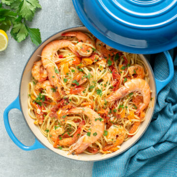 prawn linguine in a shallow casserole pot, topped with chopped parsley and whole king prawns.