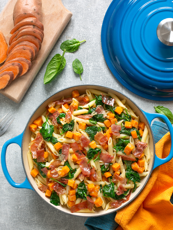 sweet potato penne pasta with crispy prosciutto adn sauteed spinach leaves served in a large blue casserole pot.