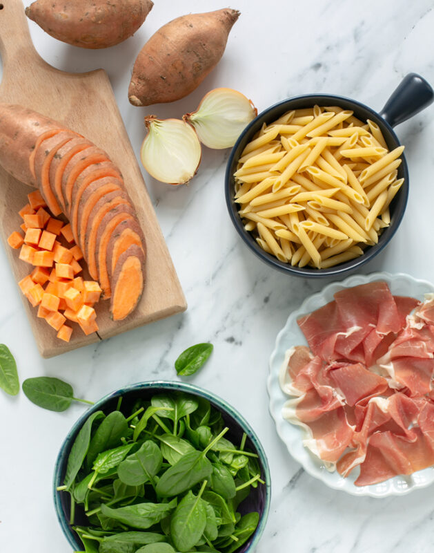 recipe ingredients: cubed sweet potato on a wood board, yellow onion, penne pasta in a small bowl, Parma ham slices on a plate, spinach leaves in a small bowl.