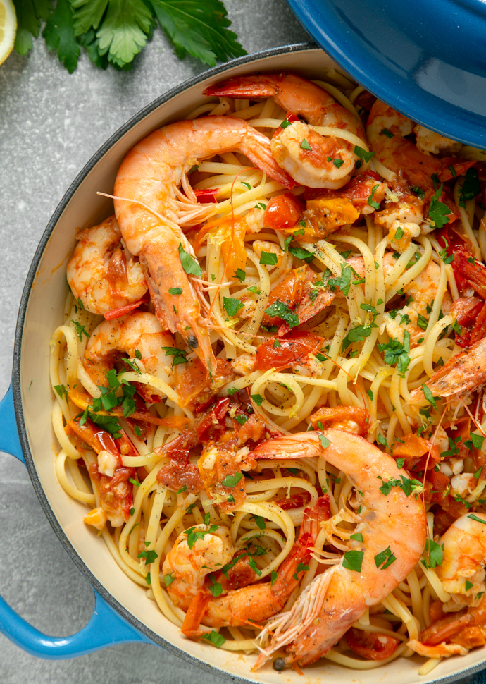 king prawn linguine topped with freshly chopped parsley in a large shallow pot.