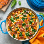 sweet potato penne pasta with crispy prosciutto adn sauteed spinach leaves served in a large pot.