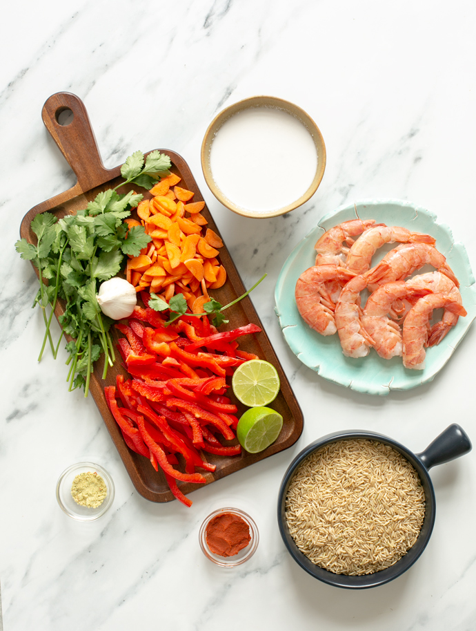 recipe ingredients: sliced carrots and red bell pepper, coconut milk, raw king prawns, brown basmati rice, thai red curry paste, stock powder, bunch of fresh coriander, garlic and lime.