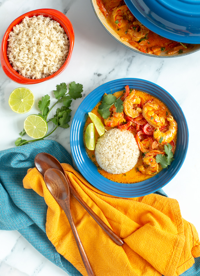 Prawn red curry served with rice, lime wedges and fresh coriander in a shallow plate, and extra brown rice on the side.