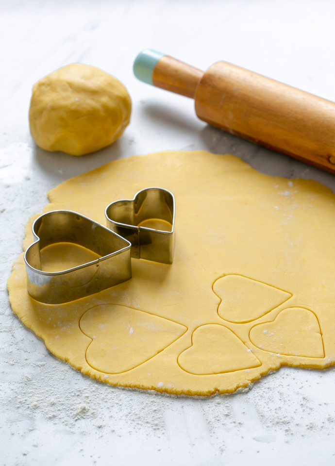 italian pastry dough rolled into a disk being cut with heart-shaped cookie cutters.
