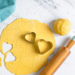 italian sweet shortcrust pastry dough rolled into a disk and cut with heart-shaped cookie cutters.