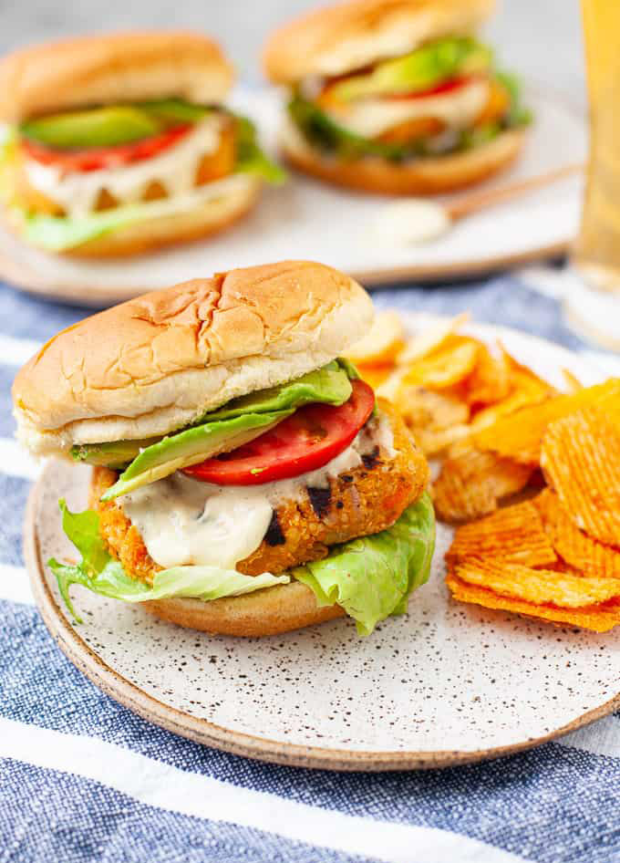 buffalo chickpea burger with lettuce, dressing and tomatoes, served with chips.