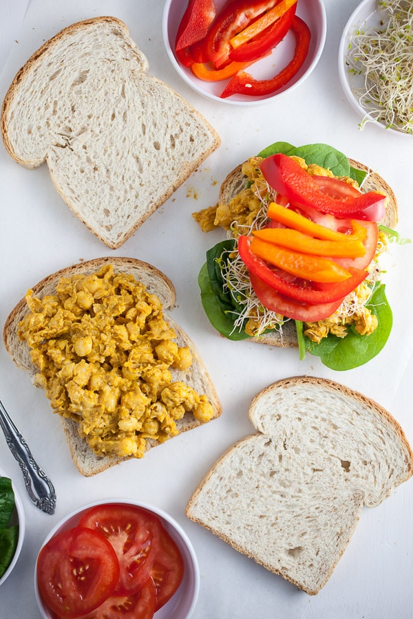 Curried chickpea salad on sandwich slices, topped with lettuce and peppers.