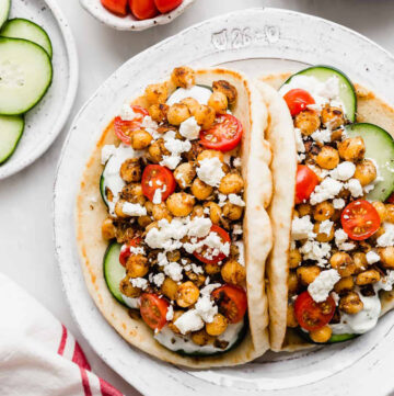 two pita bread stuffed with chickpeas and veggies gyros-style. Image for chickpea recipes round up.