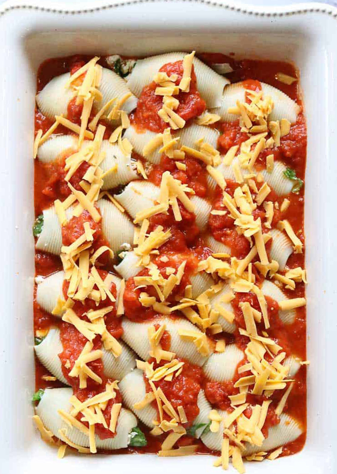 vegan stuffed shells topped with tomato sauce and vegan cheese.