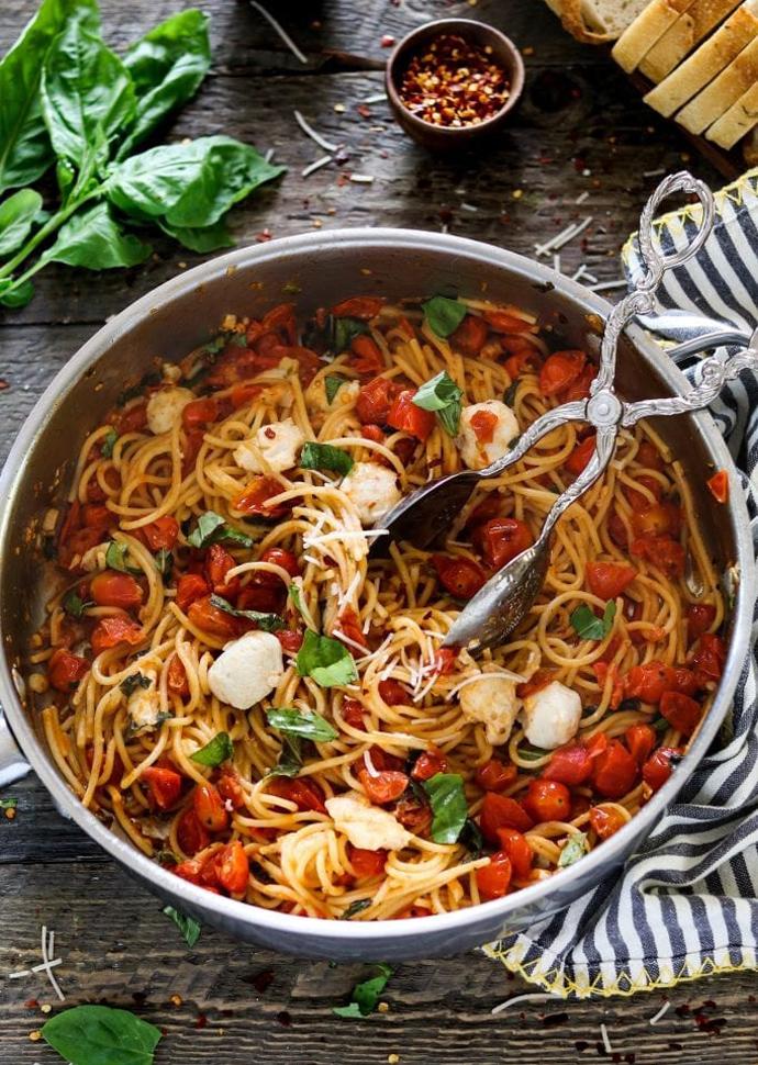 vegan caprese pasta in a pan, topped with vegan mozzarella and basil leaves.