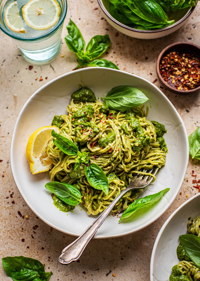 spaghetti with vegan green veggie sauce topped with basil leaves.