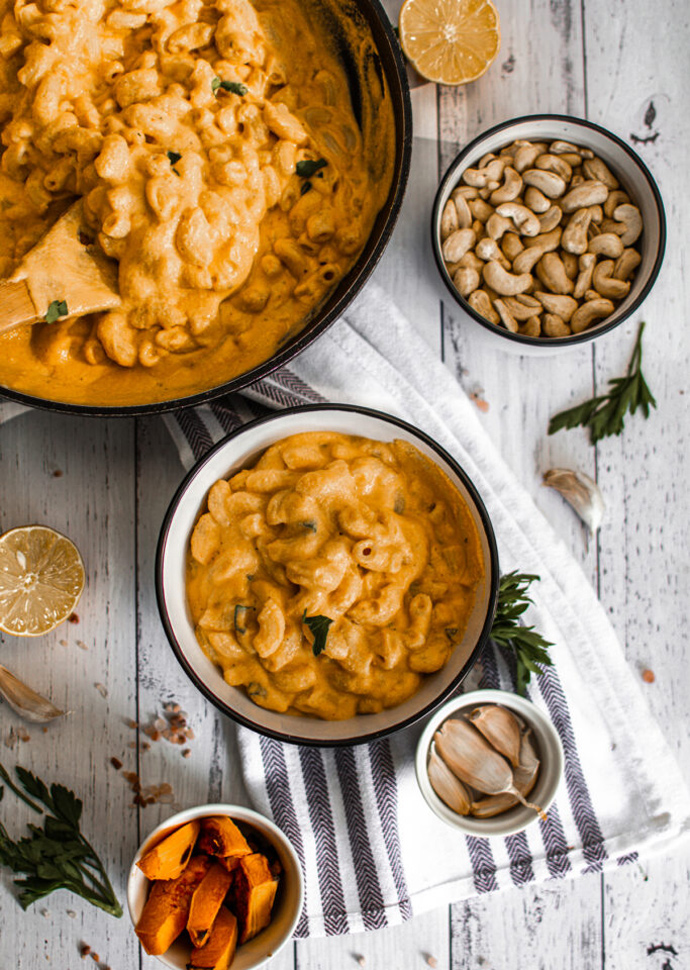 vegan pumpkin mac and cheese dividided among a large skillet and a bowl.