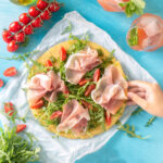 Socca pizza with Parma ham, sliced cherry tomatoes and rocket leaves.