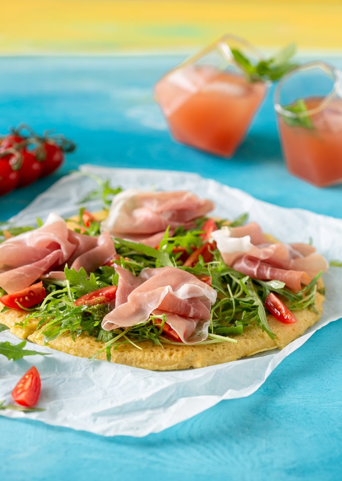 Socca pizza topped with rocket leaves, cherry tomatoes and Parma Ham slices.