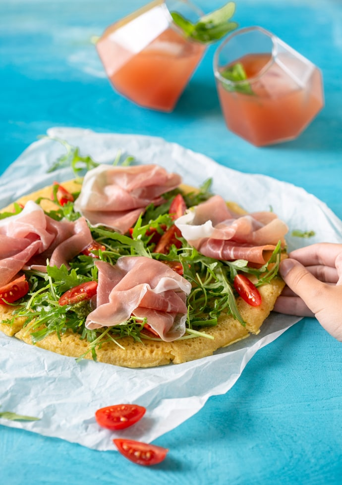 Chickpea flatbread pizza topped with Parma Ham, rocket leaves and cherry tomatoes.
