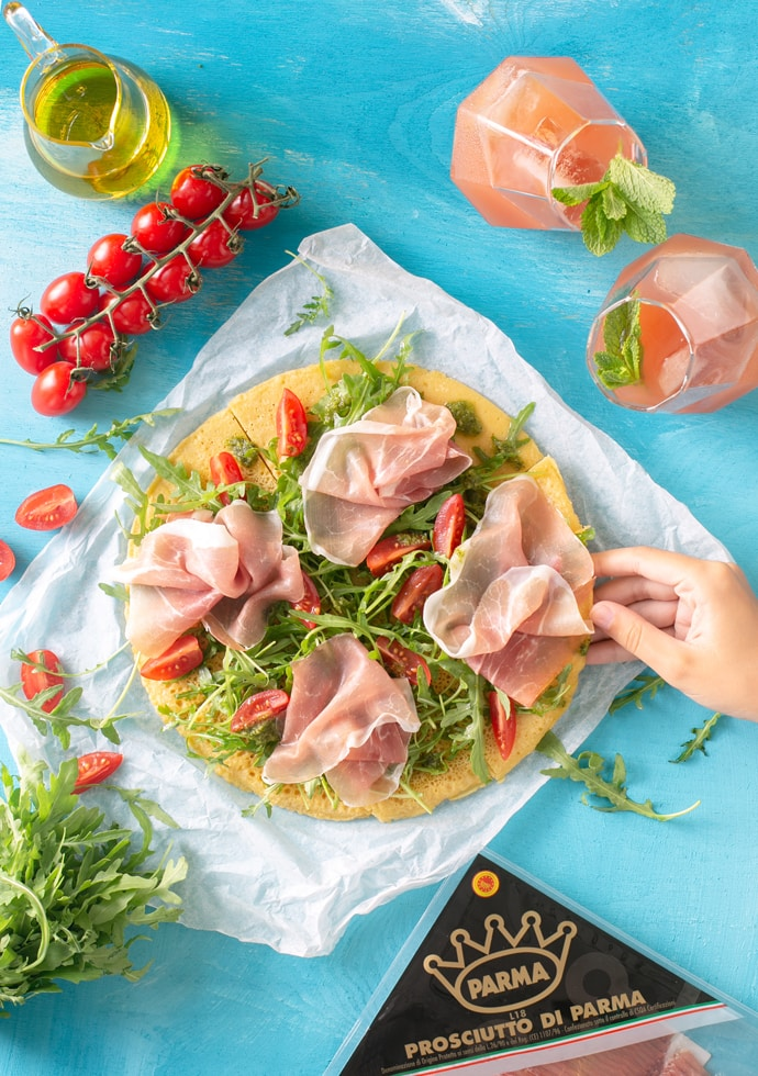 Gluten-free chickpea pizza with Parma ham, rocket leaves and sliced cherry tomatoes.