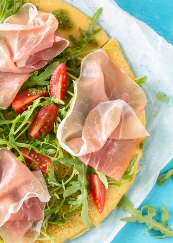 chickpea pizza crust pizza topped with rocket leaves, cherry tomatoes and Parma Ham slices.