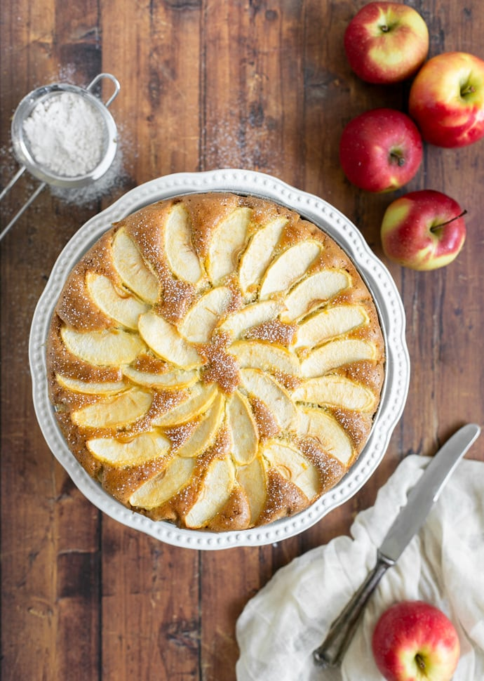 torta di mele topped with sliced apples and confectioner's sugar.