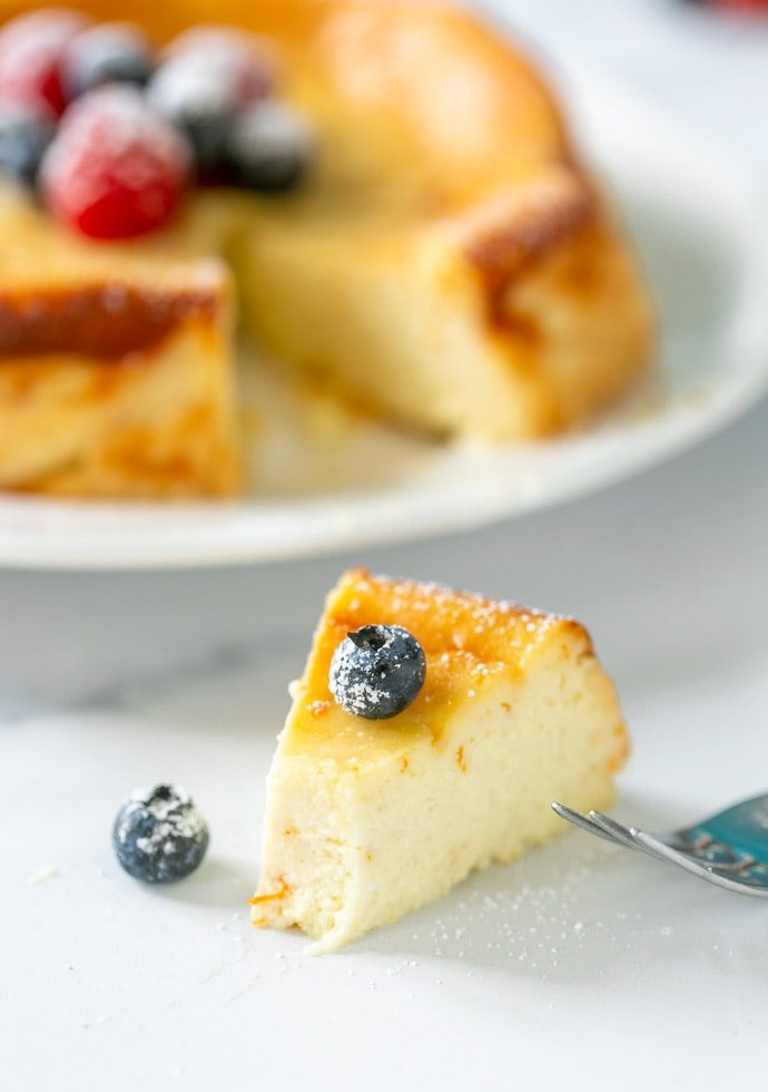 slice of ricotta cheesecake, topped with a blueberry.