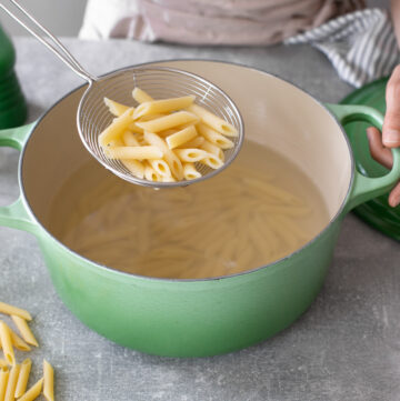 penne pasta cooked al dente in a colander over a pot with pasta.