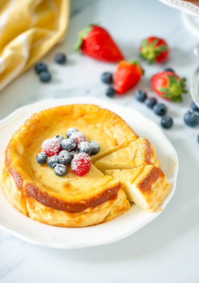 Italian ricotta cheesecake topped with fresh berries and confectioner's sugar.