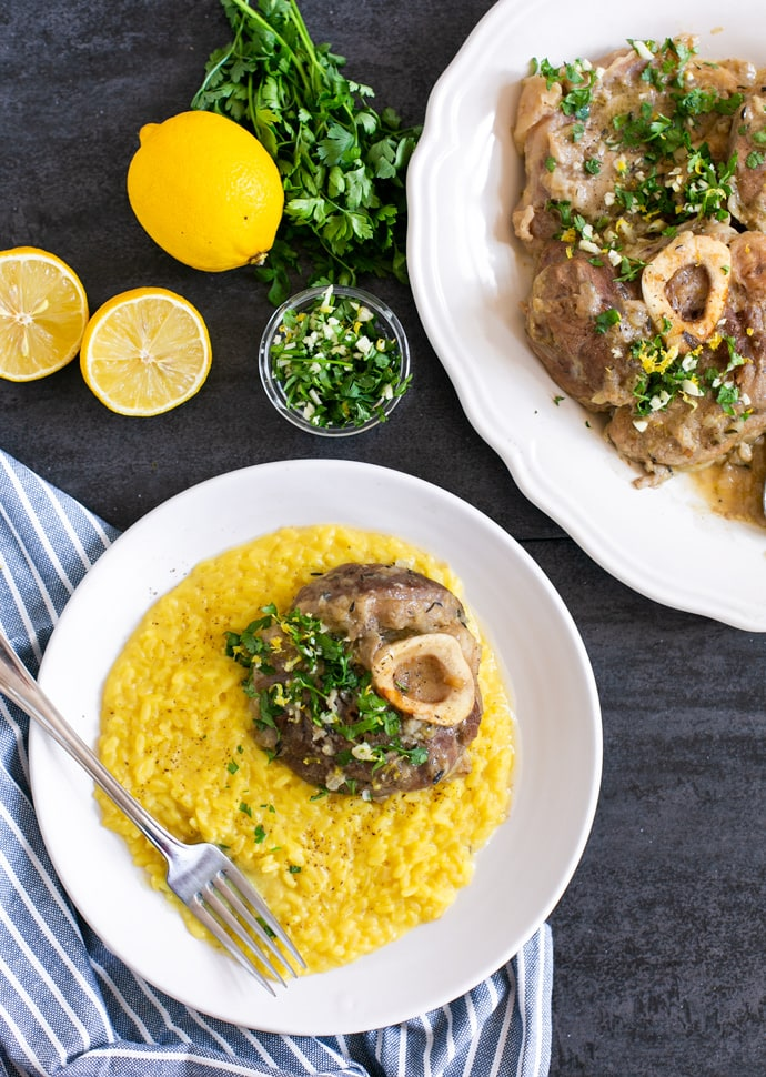 ossobuco alla milanese served over a bed of saffron risotto, and topped with gremolata.