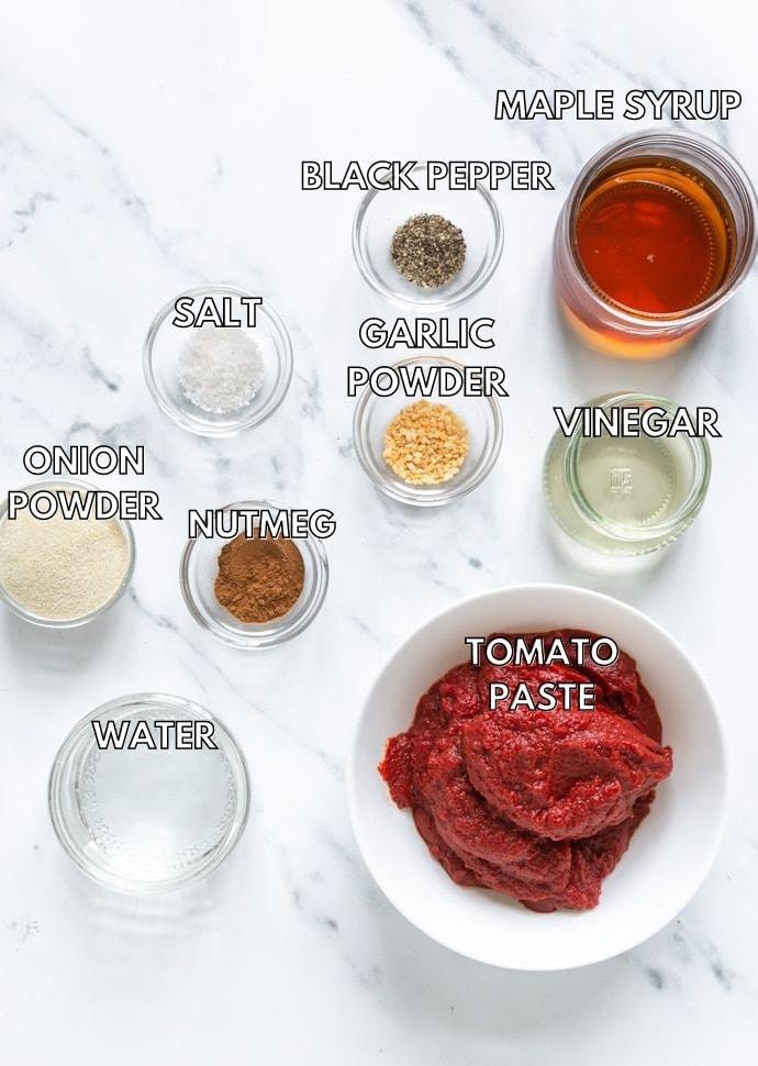 homemade ketchup ingredients: tomato paste, maple syrup, vinegar, water, nutmeg, onion powder, garlic powder, salt, pepper.